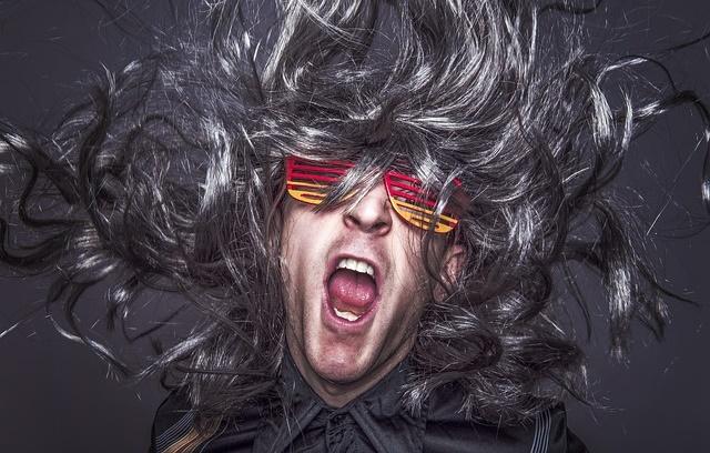 Rockowy mężćzyzna z burzą włosów i okularami