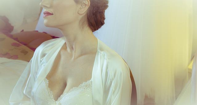 Kobieta w białym ubraniu eksponuje biust