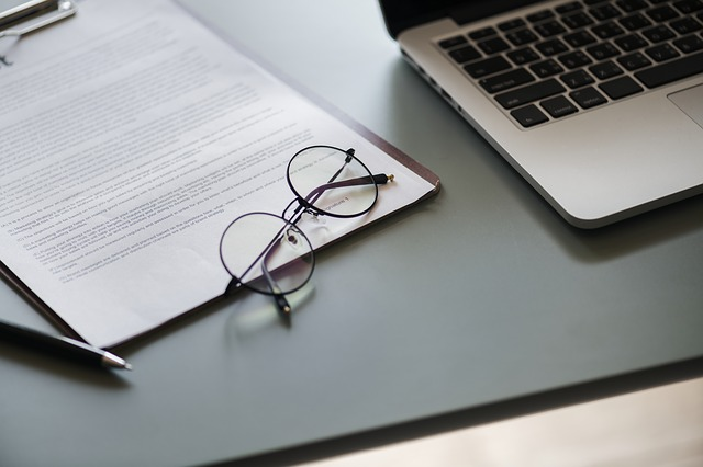 Laptop, dokumenty, okulary na biurku