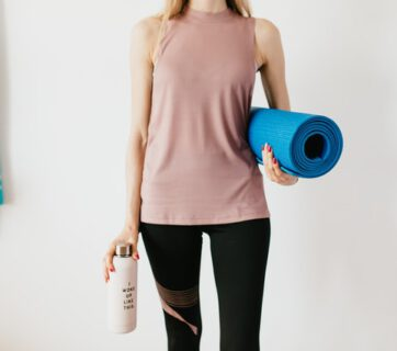 Kobieta z matą do ćwiczeń i bidonem