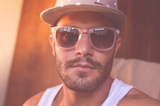 Facet z brodą i w okularach słonecznych
