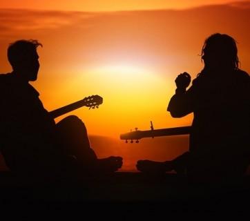 Dwoje ludzie z gitarami siedzących przy zachodzie słońca