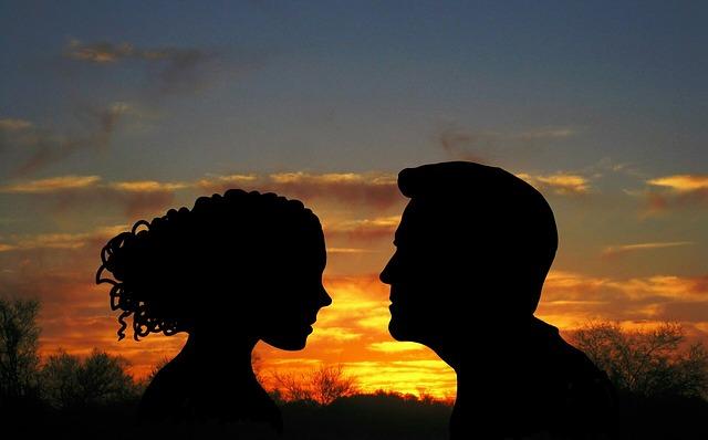 Sylwetki kobiety i mężczyzny na tle zachodzącego słońca