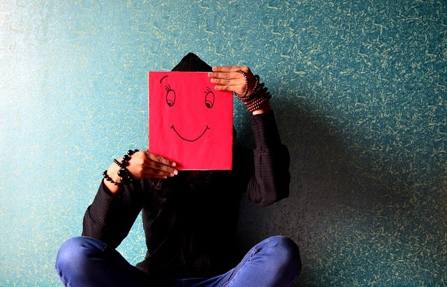 Człowiek trzymający przed twarzą kartkę z uśmiechem