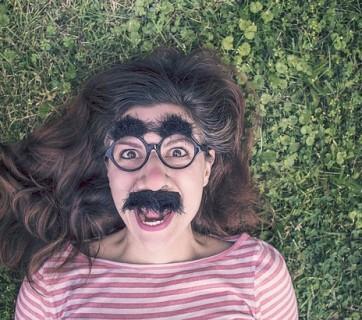 Kobieta leżąca na trawie mająca śmieszne okulary na twarzy