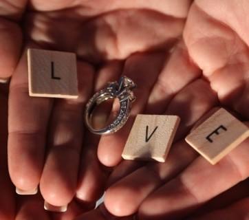 Dłonie z napisem miłość i obrączkami ślubnymi