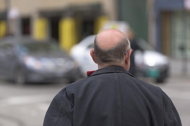 łysy mężczyzna idzie ulicą