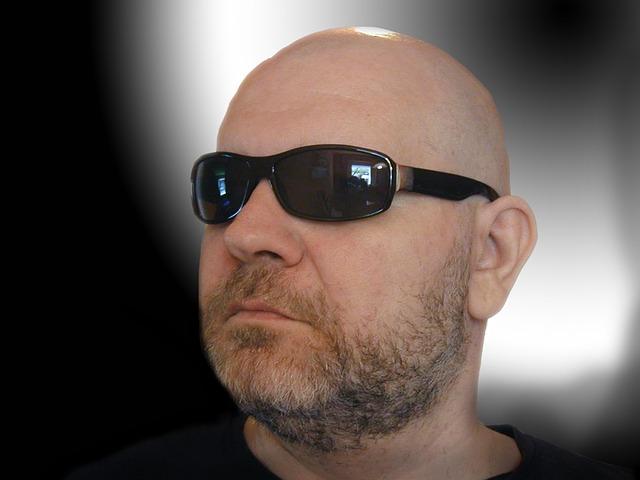 łysy facet w ciemnych okularach