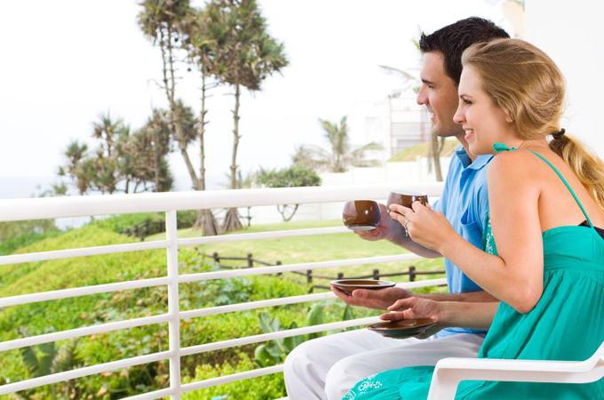 kobieta i mężczyzna na balkonie piją kawę