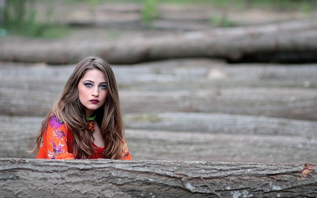 Kobieta siedząc przy belach drzewa
