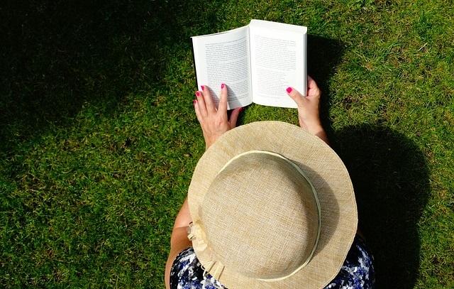 Kobieta czytająca książkę na trawie