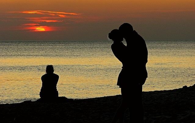 Całująca się para i siedzący na plaży samotny człowiek