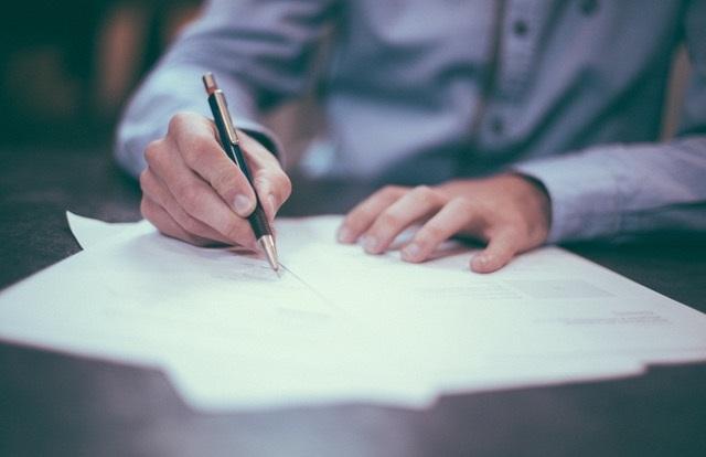 Człowiek podpisujący dokumenty