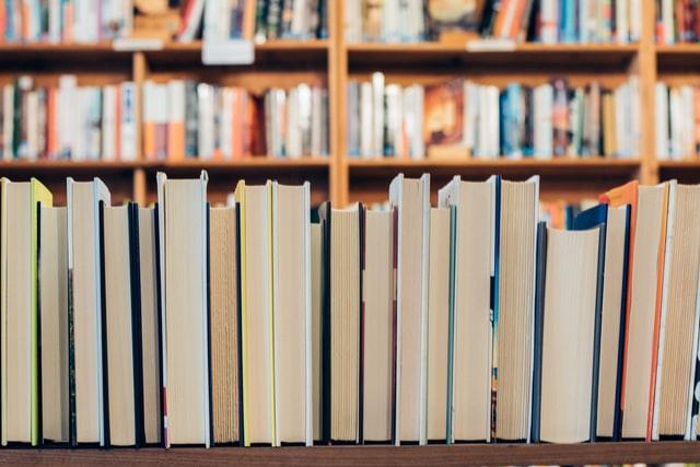 Książki ułożone w rzędzie i na półkach