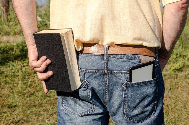 Mężyzna z książką i ebookiem w kieszeni